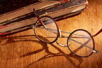 Long shadow from vintage eyewear over a wooden table