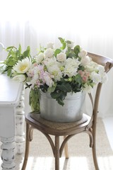 Bucket of flowers on chair