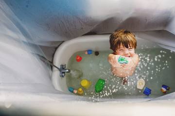 Boy (2-3) playing with toys in bath