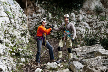 Italy, Two men wearing safety harnesses standing in front of cave