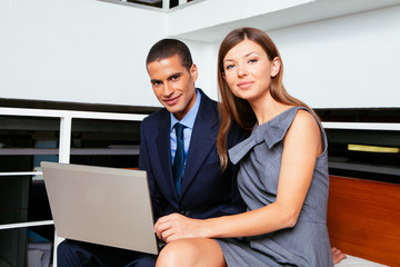 Two businesspeople using a laptop in the office