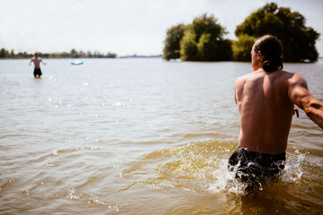 The Netherlands, Jsselmeer, Man throwing plastic flying disc across lake