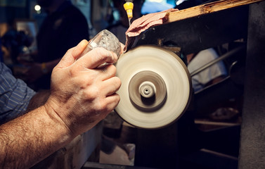 Craftsman during sanding of a crystal ashtrays