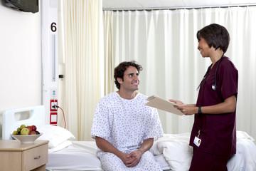 Nurse talking with man sitting on hospital bed