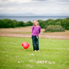 Girl (2-3) holding heart shaped balloon
