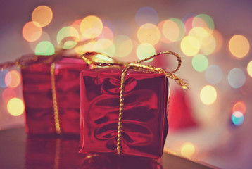 Two red Christmas gift packages on bokeh background of holiday lights.