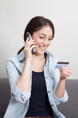 Young woman talking on telephone holding credit card