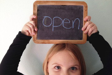Girl (6-7) holding open sign above her head