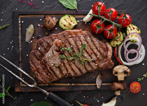 Beef steak on wooden table Poster