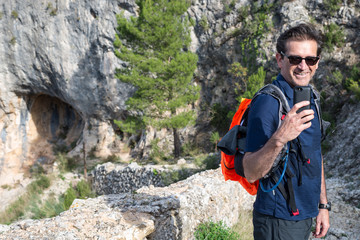 Spain, Catalonia, Tarragona, Hiker taking picture with mobile phone in mountains
