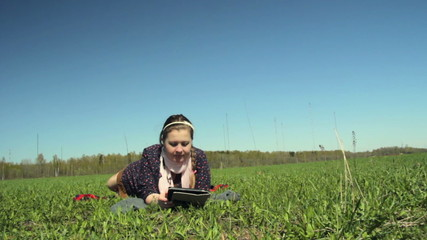 Girl lying on the grass with the tablet.