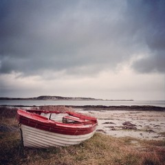 UK, Scotland, Inner Hebrides, Jura, Red and white boat on grass