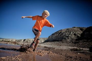 USA, Colorado, Boy (6-7) trail running through wet mud