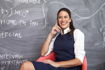 Woman Sitting By Blackboard