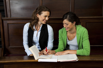 Student looking at textbook with teacher