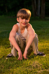 USA, Pennsylvania, Lancaster County, Lancaster, Portrait of blond boy (8-9) squatting on ground at sunset