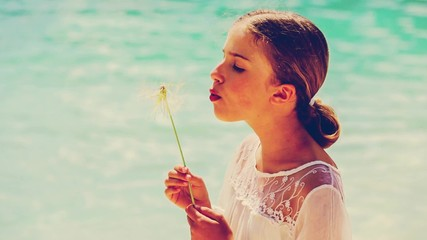 Summer joy, young girl blowing dandelion on the beach
