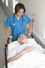 Doctor moving patient on bed along hospital corridor