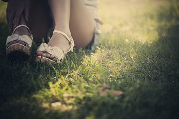 Woman Sitting On Grass, Close-Up Of Feet