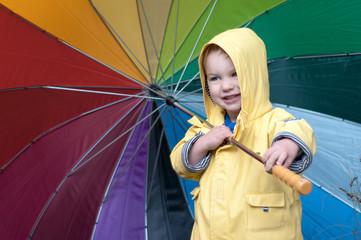 Boy holding colorful umbrella
