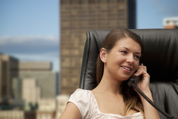 Young businesswoman using phone in office