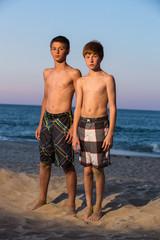 USA, North Carolina, Dare County, Nags Head, Portrait of two boys (12-13) on beach at sunset