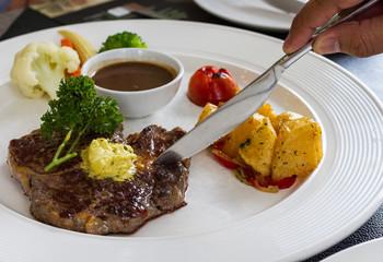 man's hand cutting on rib eye steak