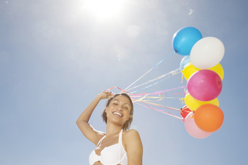 Woman holding balloons, smiling