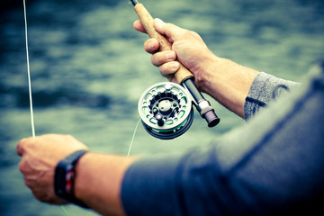 Man fly fishing, reel closeup