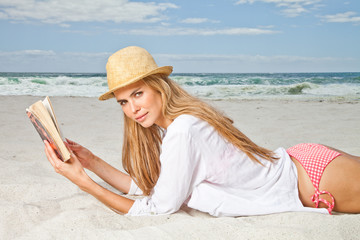 Young woman on beach with book