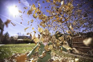 Girl in garden in swirl of autumnal leaves, portrait