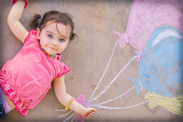 Texas, United States of America, Little Girl Laying On Ground With Chalk Drawn Balloons