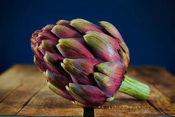 Close-up shot of artichoke flower head on wooden surface