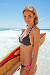 Young woman standing on beach with surfboard underarm