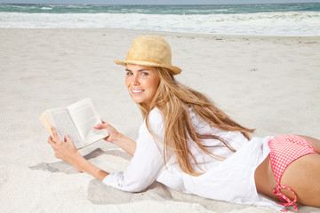 South Africa, Young woman lying on beach with a book