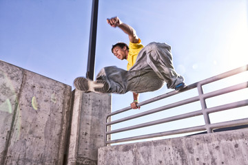 USA, Colorado, Mesa County, Grand Junction, Man making parkour jump on urban roof top
