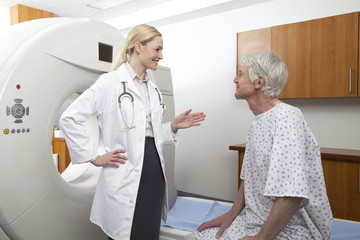 Female doctor talking to male patient next to medical scanner