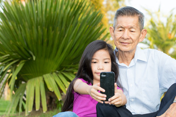 Grandfather and grandchild making self portrait with smart phone