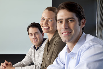 Three business people sitting at meeting table in office