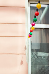Multicolored fairy lights against window and wall