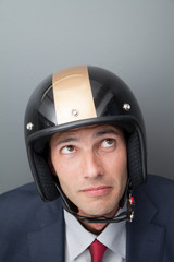 Nervous businessman wearing crash helmet