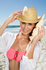 Young Woman listening to conch shell on beach