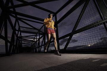 USA, Colorado, Woman jogging on bridge at night