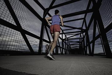 USA, Colorado, Woman jogging across bridge at dusk