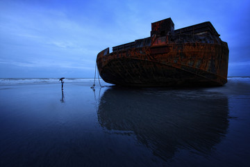 Boy (14-15) dwarfed by huge abandoned barge