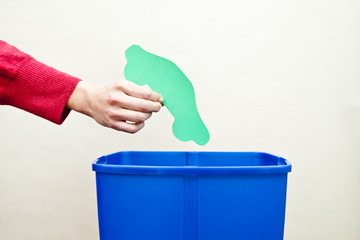 Womans hand dropping car shape paper cut out into recycling bin