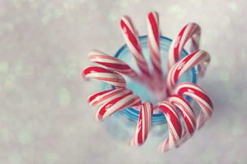 Red and white striped candy canes in blue mason jar against glittering background