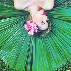 Australia, Woman lying on palm leaf