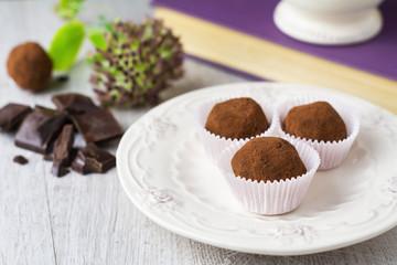 Three chocolate truffles on white plate