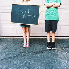 Girl (8-9) and boy (12-13) with blackboard sign